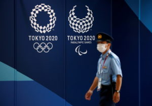 A policeman walks past Tokyo 2020 Olympic signage at the Main Press Center in Tokyo