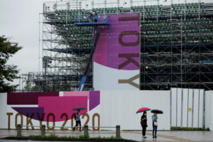 Construction workers are seen next to a scaffoldings for the spectator seats at Aomi Urban Sports Park in Tokyo