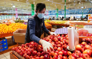 Wearing a mask and gloves, a worker re-stocks apples in a Asian grocery store in Falls Church, Virginia