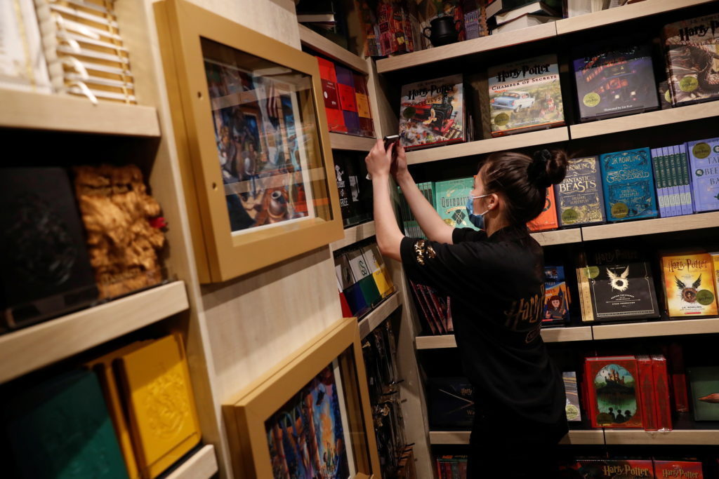 An employee of the Harry Potter New York store pulls a book from a shelf during press preview in the Flatiron district of ...