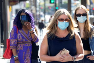 FILE PHOTO: People wearing face protective masks walk on Hollywood Blvd during the outbreak of the coronavirus disease (CO...