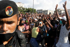 People react during protests against and in support of the government, in Havana