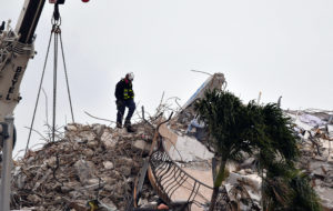 Jul 6, 2021; Surfside, FL, USA; A crew of search and rescue workers on top of what was once Champlain Towers South condomi...