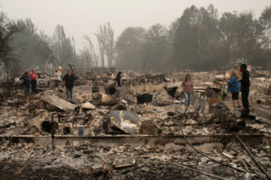 The Webber family searches for belongings through their home, which was gutted by the Almeda fire, in Talent, Oregon