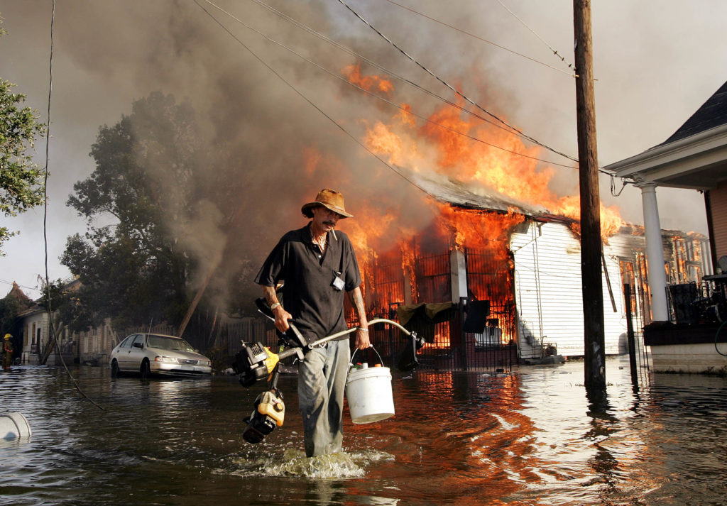 A man makes his way out of flood waters as a home burns in the seventh ward of New Orleans during the aftermath of Hurrica...