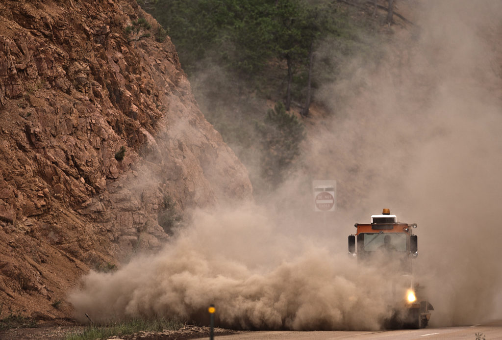 Dust is kicked up in the air crews work to remove dirt runoff in Manitou Springs