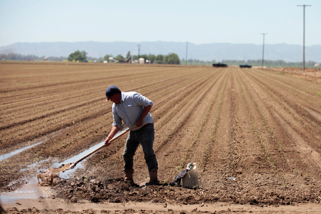 A farm worker repairs irrigation pipes during spring planting in the Central Valley in California. REUTERS/Hyungwon Kang