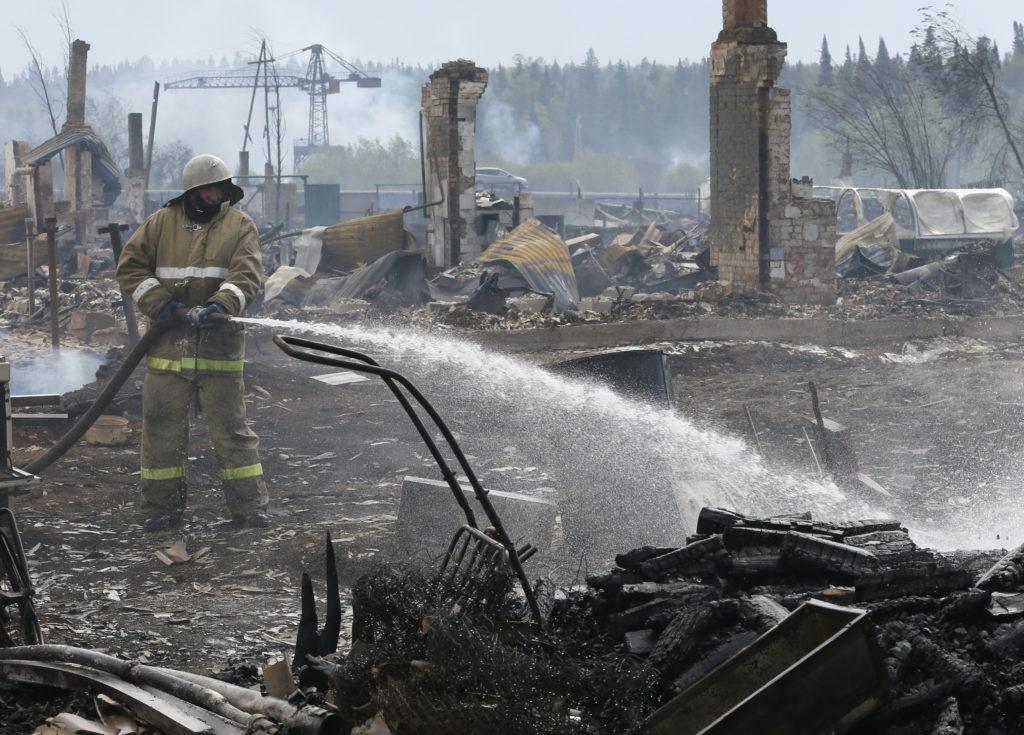 A firefighter works amidst the debris of burnt houses following recent wildfires in Krasnoyarsk region