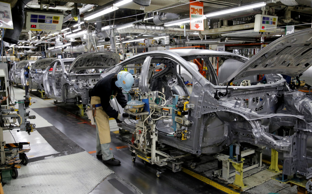 An employee works on an assembly line of the Toyota Motor Corp's Prius hybrid car at the Tsutsumi plant in Toyota