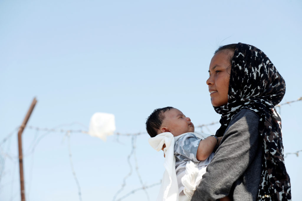 An Afghan woman and her month-old son are seen outside the new temporary camp for migrants and refugees on Lesbos island