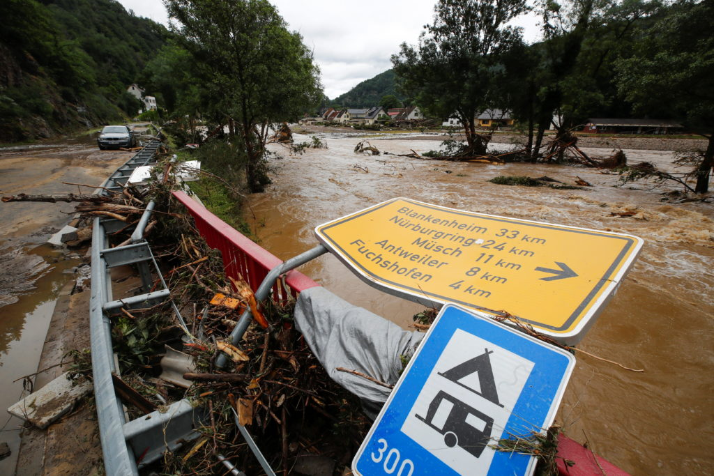 A collapsed sign is seen next to a river at a flood-affected area in Schuld