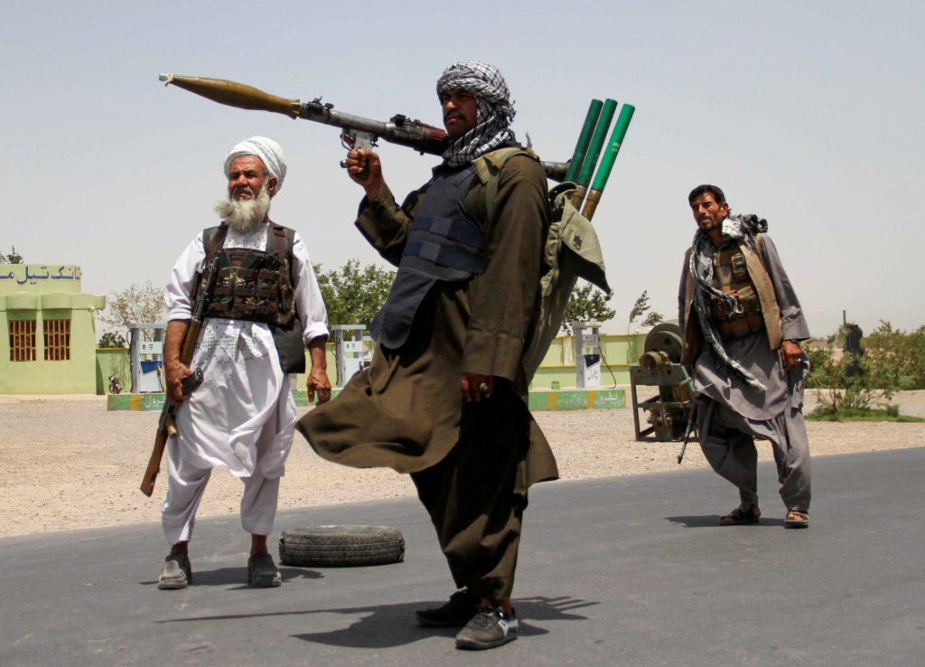 FILE PHOTO: Former Mujahideen hold weapons to support Afghan forces in their fight against Taliban, on the outskirts of He...