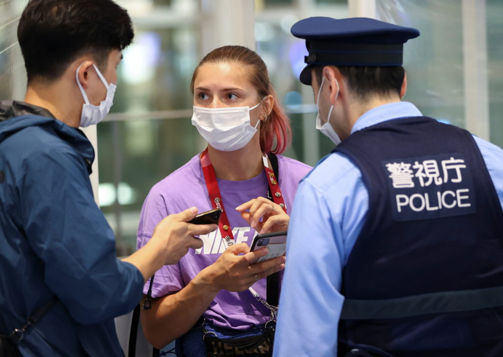Belarusian athlete Krystsina Tsimanouskaya talks with a police officer at Haneda international airport in Tokyo, Japan
