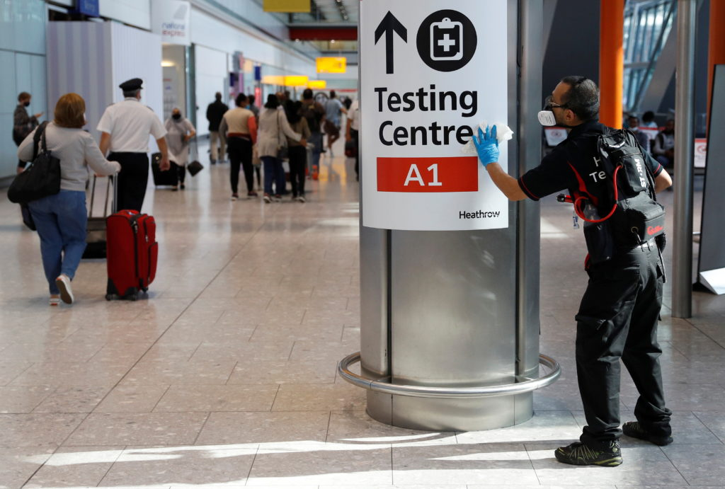 A worker sanitises a sign at the International arrivals area of Terminal 5 in London's Heathrow Airport