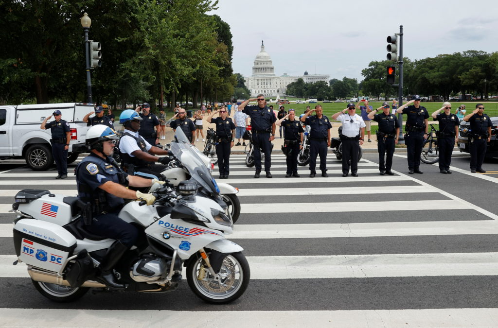 Law enforcement officers salute as a ceremonial procession in honor of a police officer wounded at the Pentagon passes the...