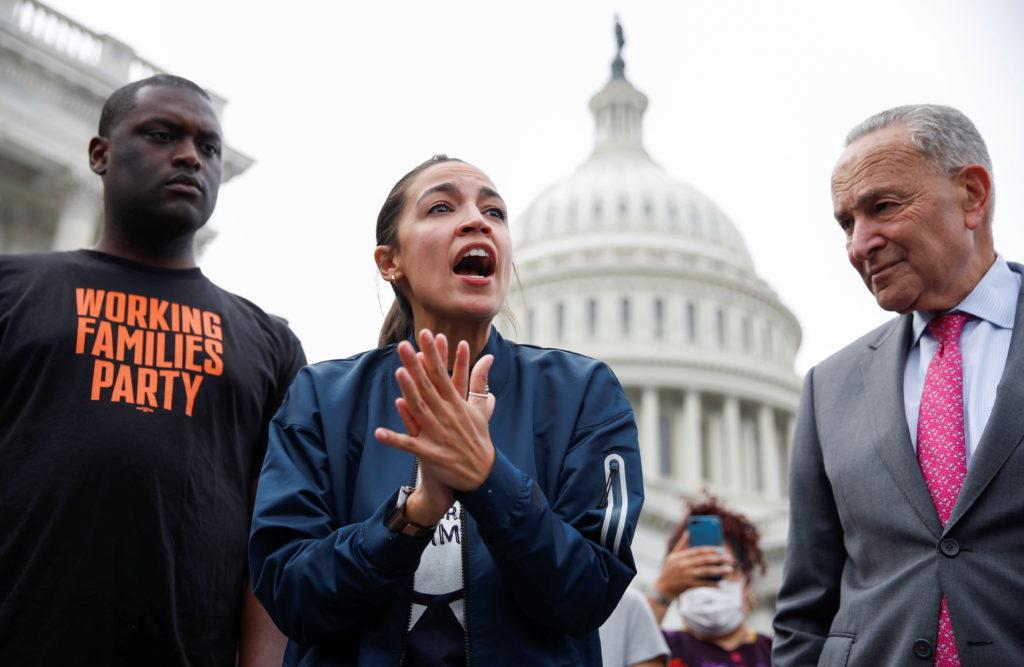 Rep. Alexandria Ocasio-Cortez speaks on Capitol Hill with Rep. Mondaire Jones and Senate Majority Leader Chuck Schumer in ...