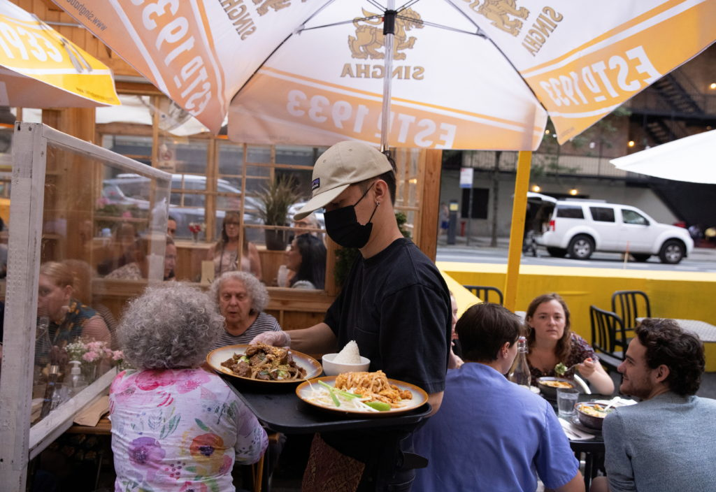 People eat at a restaurant in Manhattan, New York