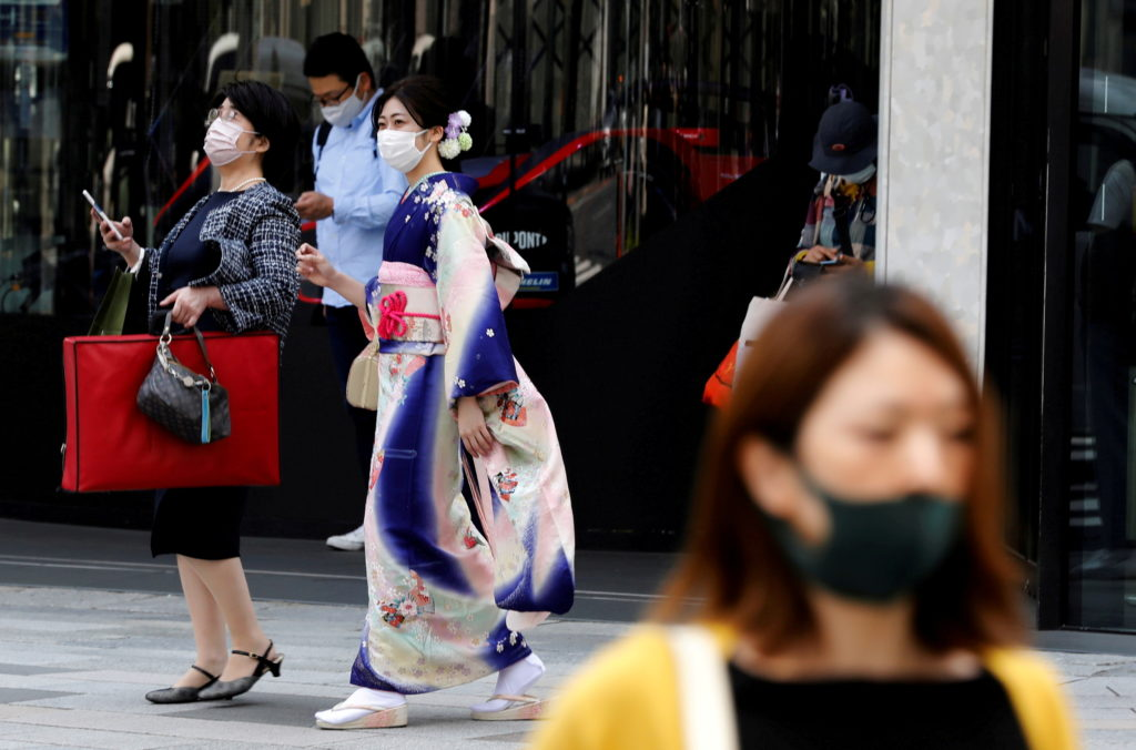 FILE PHOTO: A woman in kimono clad and pedestrians wearing protective face masks, make their way at a shopping district on...