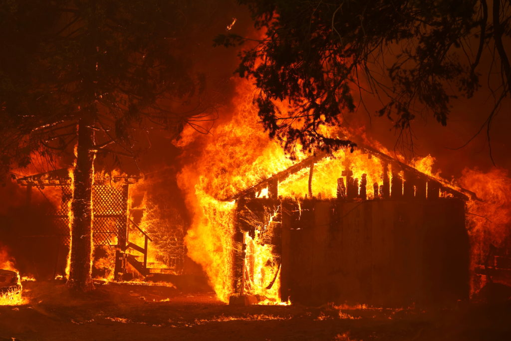 A house is fully engulfed by flames at the Dixie Fire, a wildfire near the town of Greenville