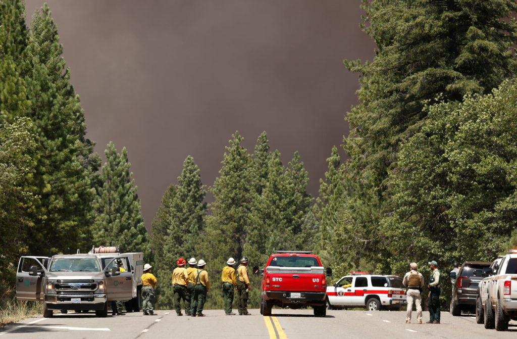 Firefighters and police watch dark smoke at the Dixie Fire near Greenville