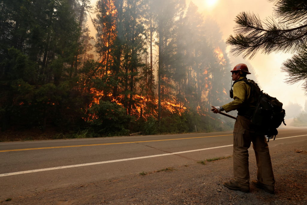 Firefighter David Molter monitors flames at the Dixie Fire near Greenville