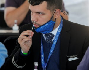 FILE PHOTO: A United Airlines employee swabs his nose for a coronavirus disease (COVID-19) test to attend a mass reunion e...