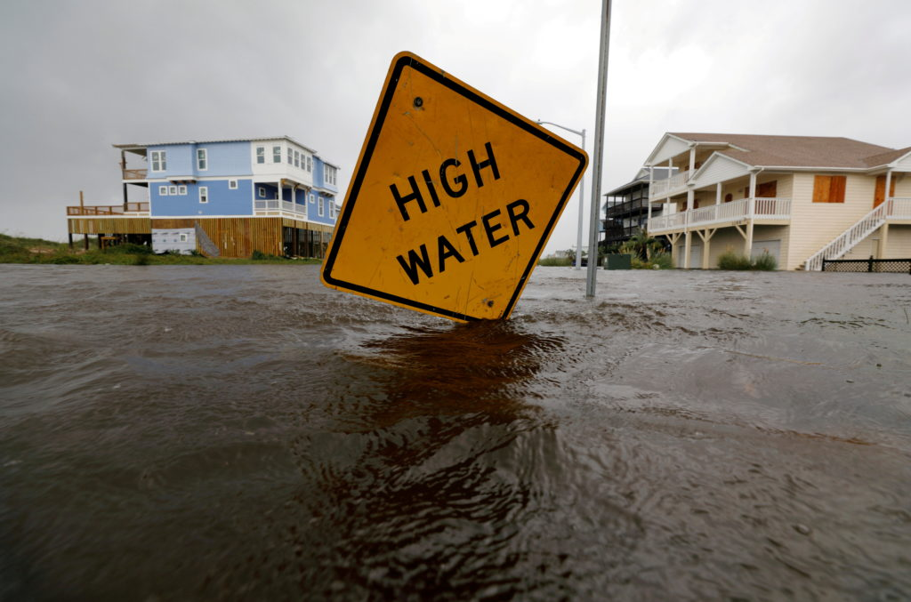FILE PHOTO: Flood waters lap at a high water warning sign that was partially pushed over by Hurricane Florence on Oak Isla...