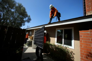 FILE PHOTO: Workers lift a solar panel onto a roof during a residential solar installation in Scripps Ranch, San Diego, Ca...