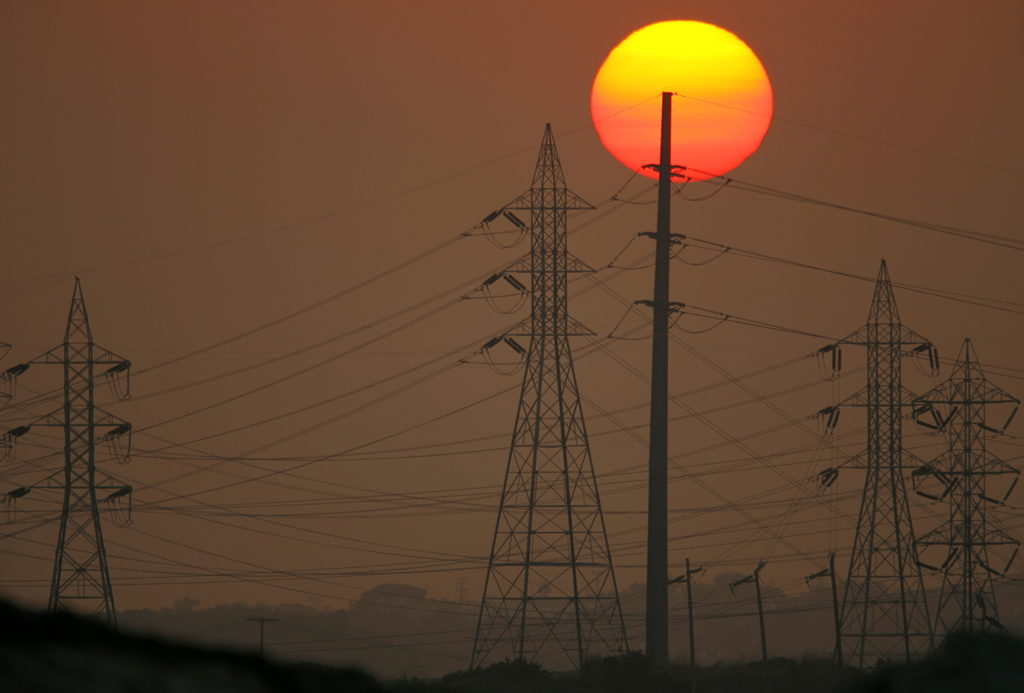 FILE PHOTO: Sun sets behind power lines in California