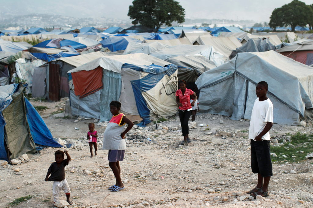 FILE PHOTO: 2011 photo shows Haitians made homeless in previous year's earthquake standing outside their tents