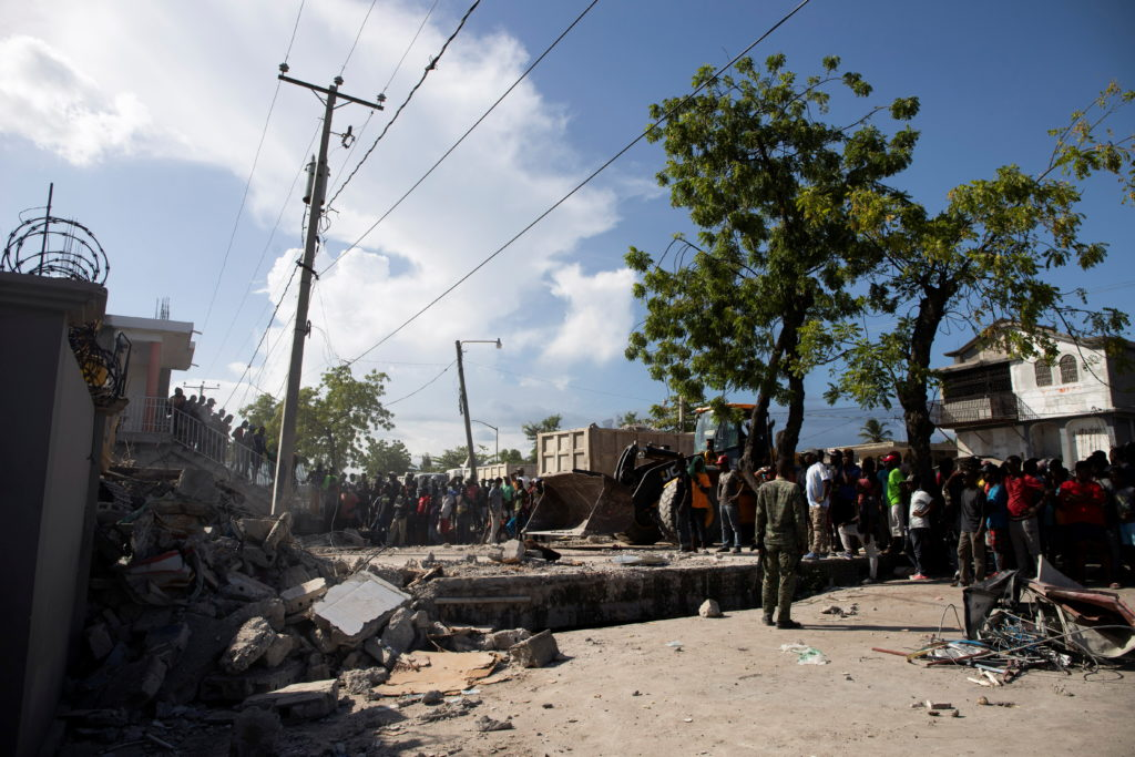 People look at a damaged house after a 7.2 magnitude earthquake in Les Cayes