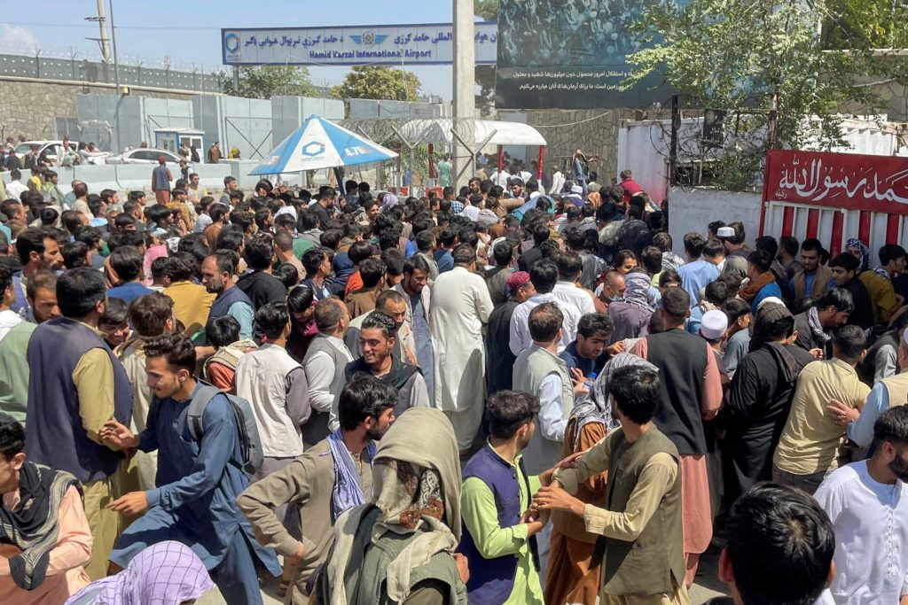 A crowd of people scrambles to try to get into Hamid Karzai International Airport in Kabul, Afghanistan, on August 16, 2021.