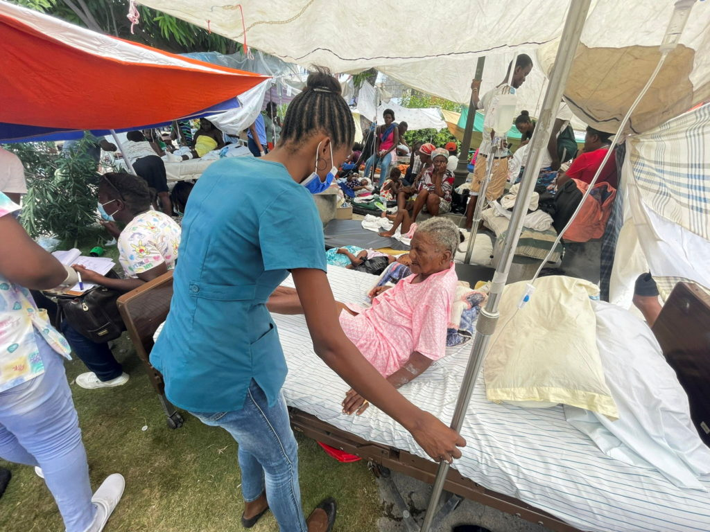 A woman in a blue shirt and jeans helps an older woman in a pink dress on a medical bed under a crowded outdoor tent following a 7.2 magnitude earthquake.