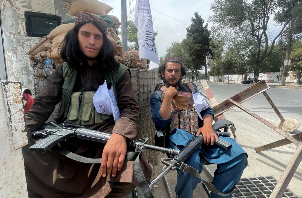 FILE PHOTO: Members of Taliban forces sit at a checkpost in Kabul