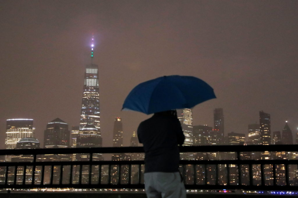 A person with an umbrella stands in falling rain while looking toward New York City ahead of Hurricane Henri in Liberty St...