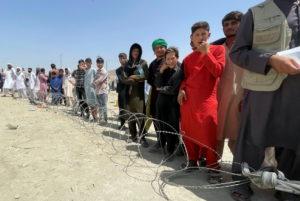 People wait outside Hamid Karzai International Airport in Kabul