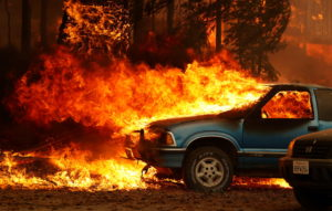 Wind-driven flames shoot horizontally out of the windshield of a car on fire at the Dixie Fire, a wildfire near the town o...