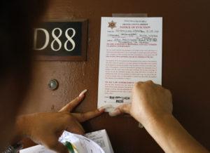Orange County sheriff's deputy Ramona Figueroa posts an eviction notice on an apartment in Fullerton, California