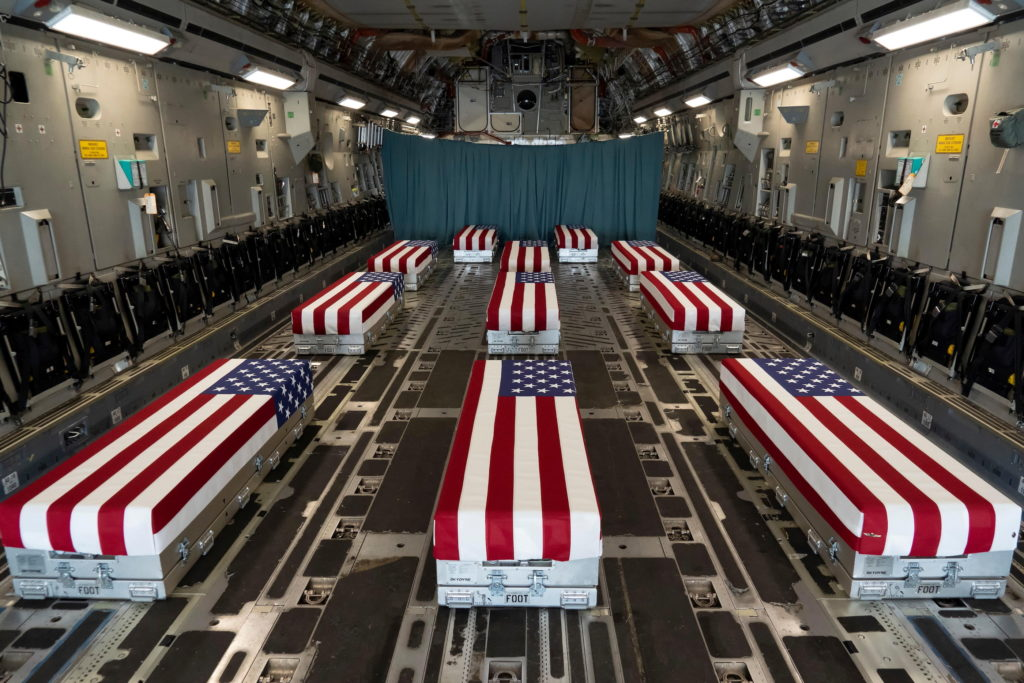 Flag-draped transfer cases line the inside of a C-17 Globemaster II prior to a dignified transfer