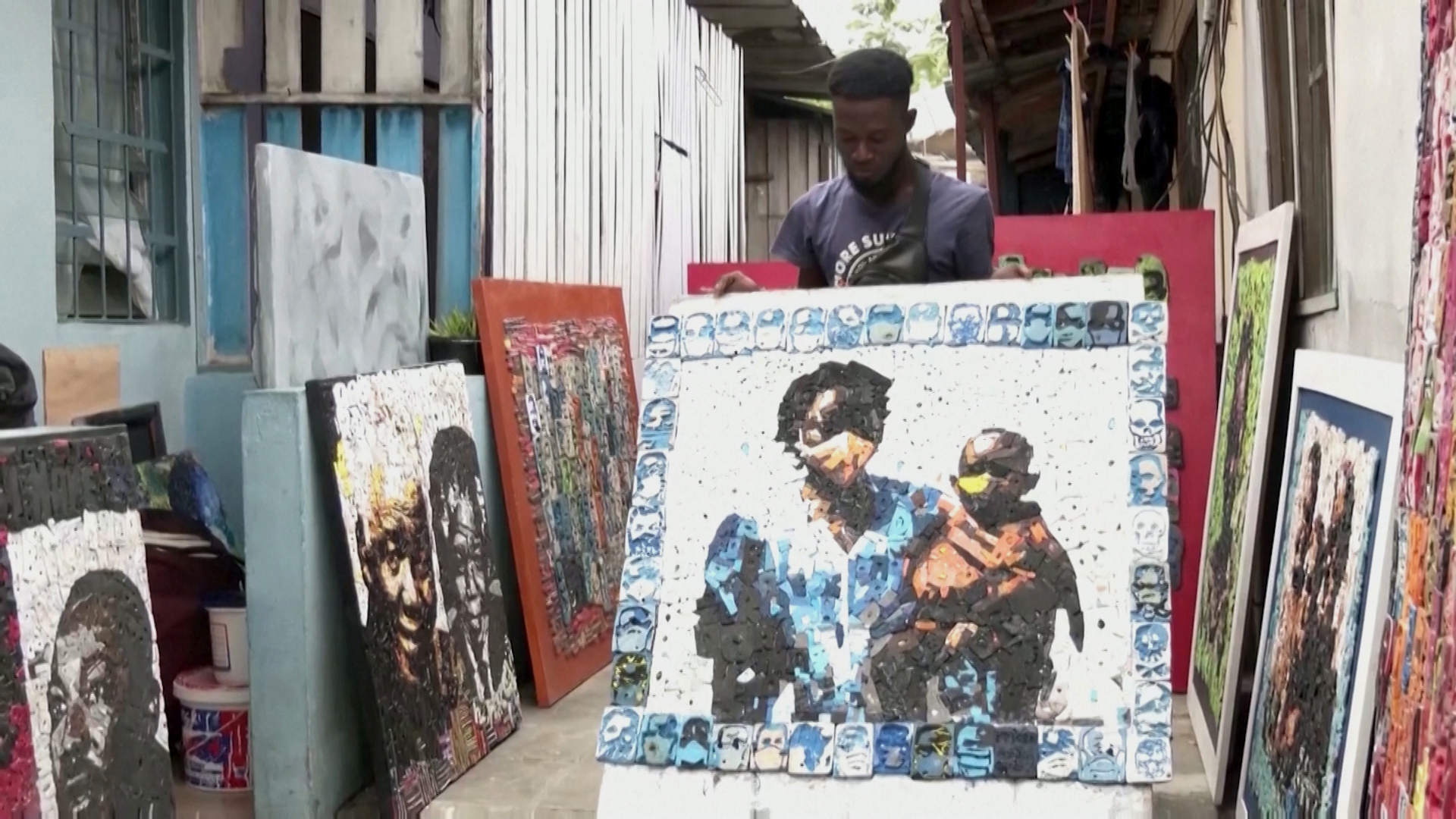 Ivorian painterAristideKouame looks at one of his collages crafted from recycled flip-flops.