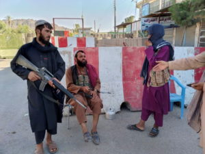 Taliban fighters stand guard at a check point in Farah