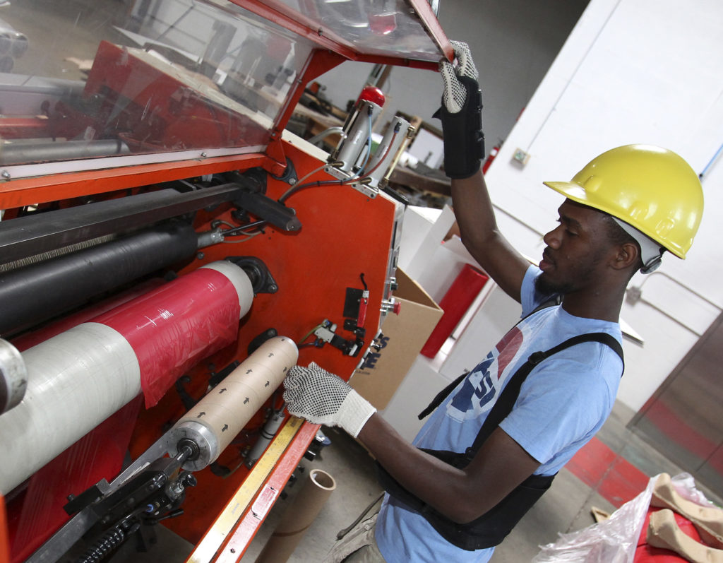 Worker Dujuan Brown loads an 18 inch plastic roll into a machine at the Wrap-Tite manufacturing facility in Solon, Ohio