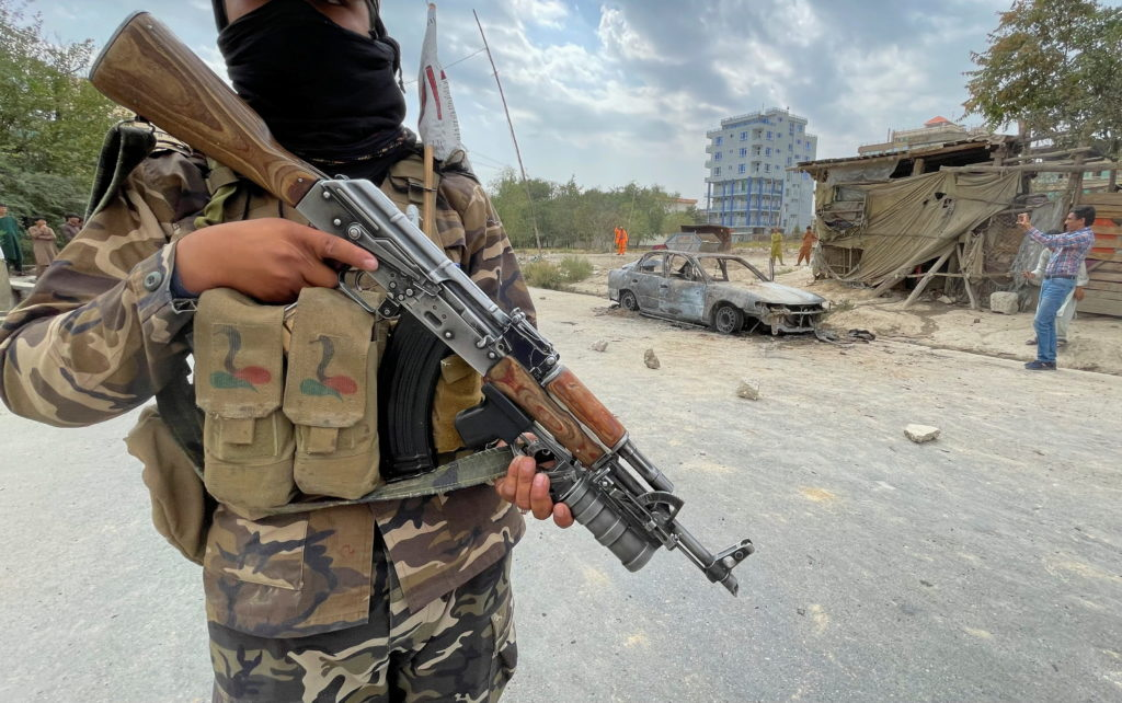 A member of Taliban forces stands guard as Afghan men take pictures of a vehicle from which rockets were fired, in Kabul