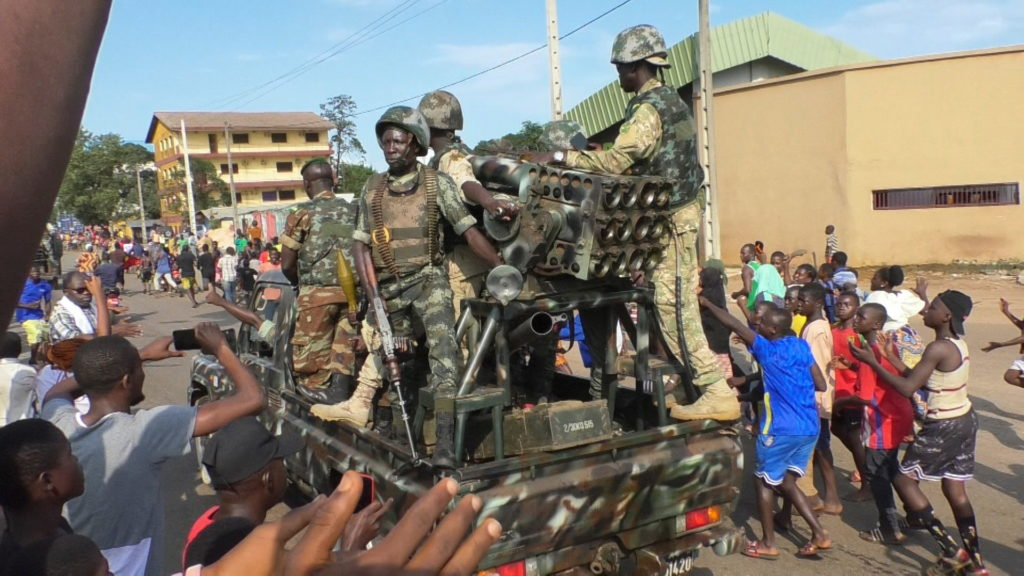 Residents cheer at army soldiers as they celebrate the uprising in Conakry