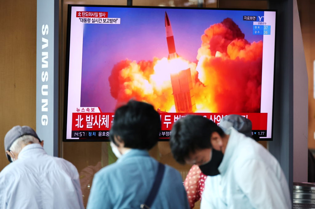 People watch a TV broadcasting file footage of a news report on North Korea firing what appeared to be a pair of ballistic...