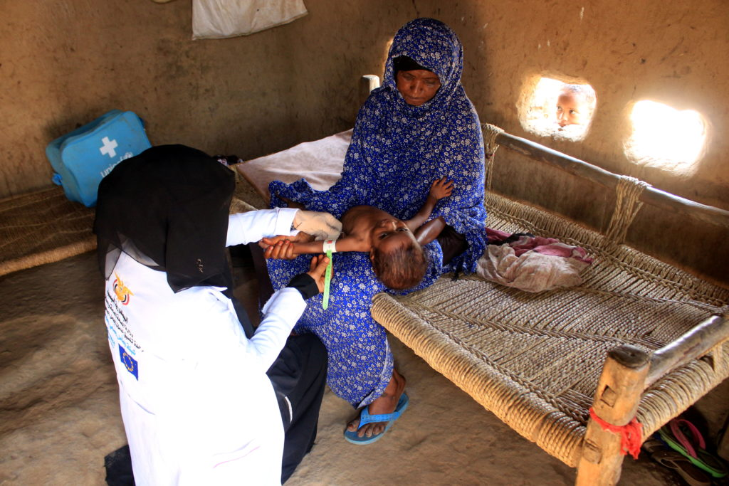 Volunteer health worker Ashwaq Muharram measures the arm of a girl to assess her nutritional status in Abs