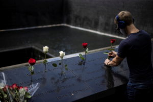 A man places roses at the 9/11 Memorial ahead of the 20th anniversary of the September 11 attacks in Manhattan, New York C...
