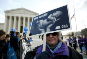 A protester holds up a sign in front of the U.S. Supreme Court in Washington