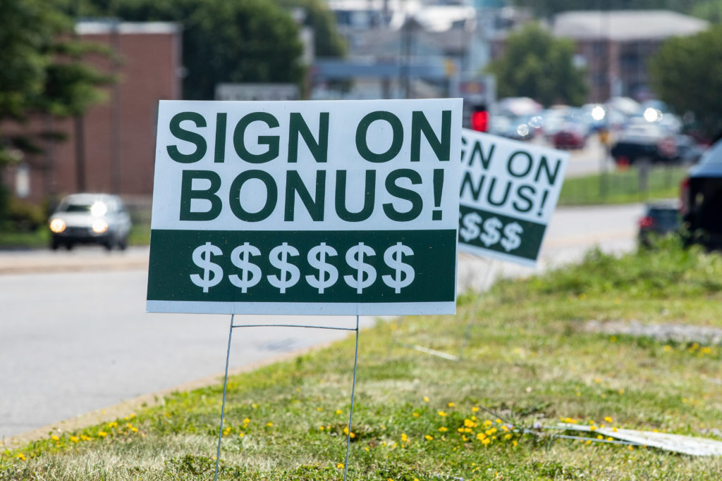 """A sign reading """"sign on bonus"""" is seen at a Perkin's"""