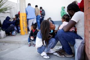 Migrants from Haiti stand near the Zaragoza-Ysleta international border bridge after being deported from the United States...